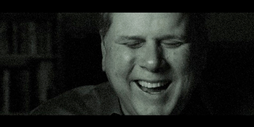 A black and white image of Tommy Edison laughing on screen.