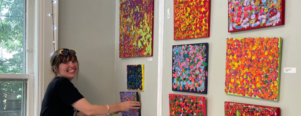 The image above shows a young woman hanging artwork at one of Friends Life Community's events.